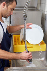 Kitchen worker washing dishes in a commercial kitchen